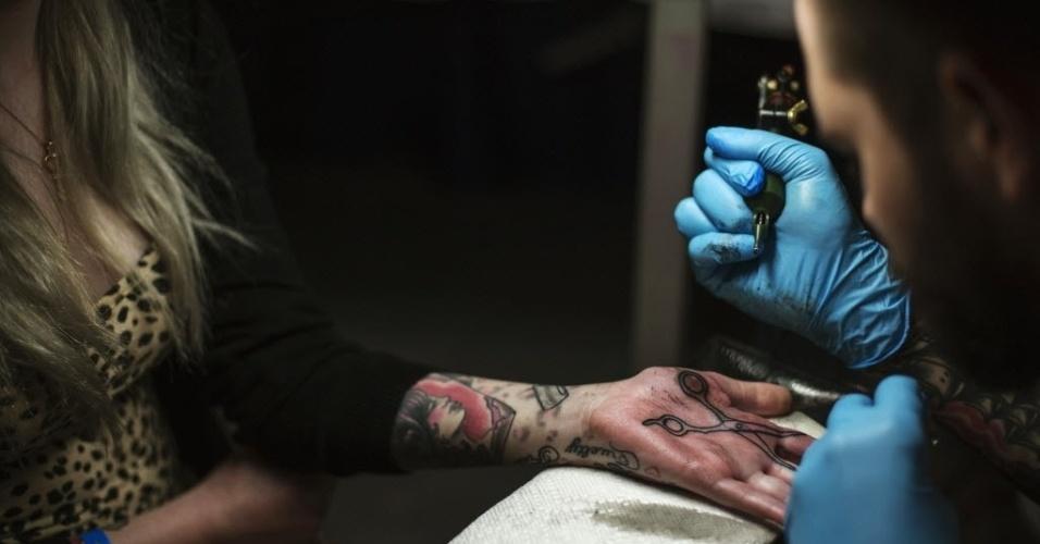 18.mai.2013 - Tatuador desenha tesoura na mão de mulher durante evento sobre tatuagem em Nova York