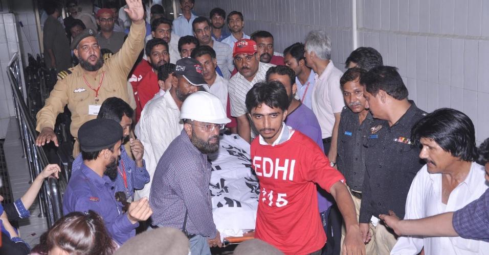 19.mai.2013 - Corpo de Zahra Shahid, uma líder sênior do partido paquistanês Tehrik-e-Insaf, é carregada na madrugada deste domingo (19) em Karachi (Paquistão). Zahra foi morta na noite deste sábado (18) por três atiradores desconhecidos fora de sua casa. O Tehrik-e-Insa acusa o partido Movimento Mutaida Quami pelo assassinato