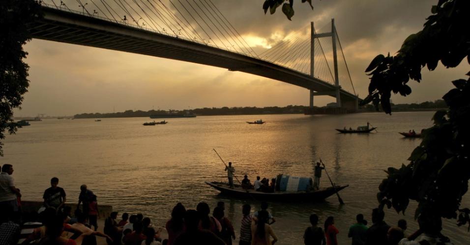 19.mai.2013 - Sol aparece entre nuvens de chuvas no rio Ganges, em Calcutá, na Índia, neste domingo (19)