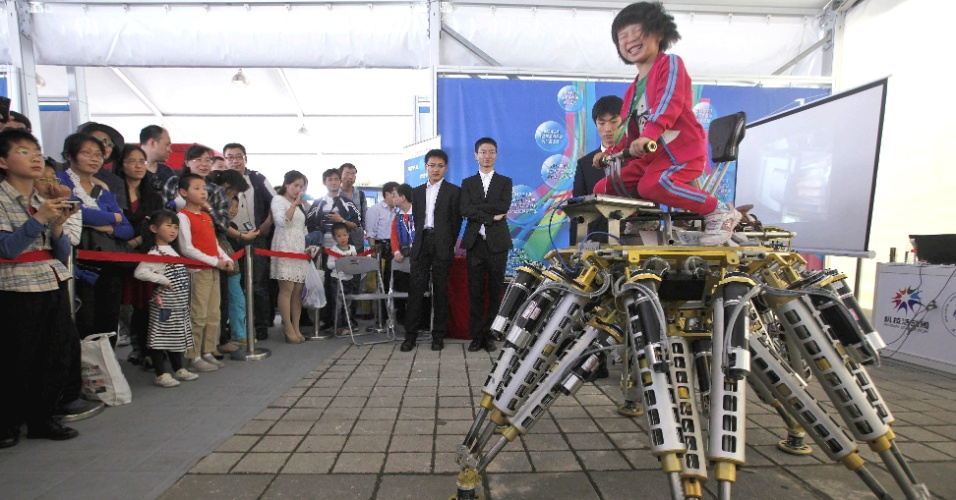 19.mai.2013 - Visitantes observam garota andando em robô feito pela Universidade Shanghai Jiaotong, em feira de tecnologia em Xangai, na China
