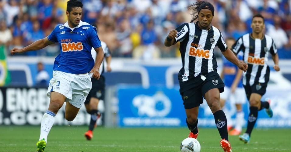 Ronaldinho avança sendo observado por Léo, do Cruzeiro