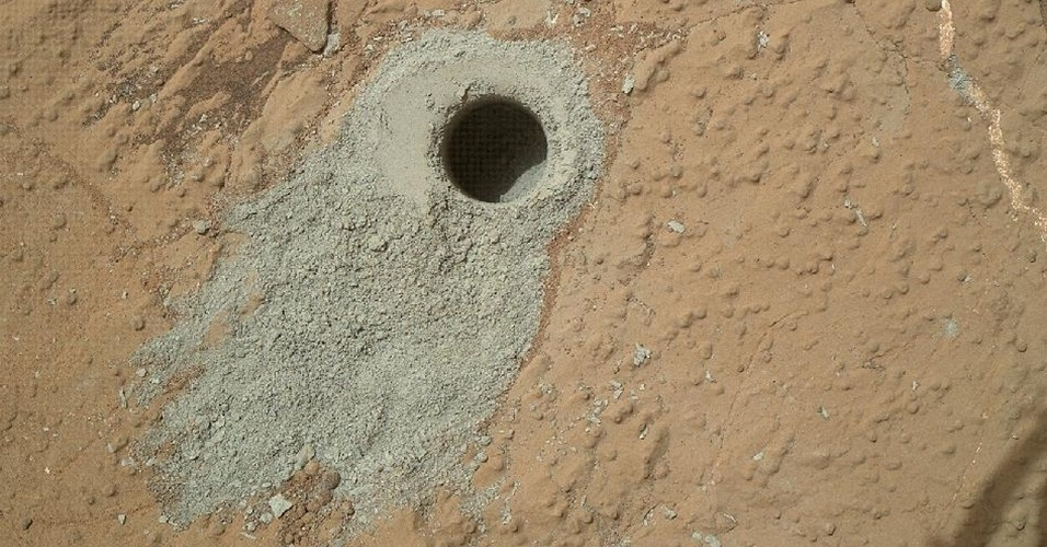 20.mai.2013 - Curiosity coletou amostras do solo de Marte ap&#243;s perfurar seu novo alvo, a &#225;rea rochosa Cumberland, durante o  279&#186; dia de sua miss&#227;o (que corresponde a 19 de maio), anunciou a Nasa (Ag&#234;ncia Espacial Norte-Americana). O buraco, feito dois dias depois de o rob&#244; chegar ao local, tem 1,6 cent&#237;metro de di&#226;metro e 6,6 cent&#237;metros de profundidade. A nova an&#225;lise do rob&#244; pretende confirmar os resultados da primeira perfura&#231;&#227;o ocorrida na rocha John Klein, a exatos 2,75 metros de dist&#226;ncia, e que indicou um ambiente favor&#225;vel ao desenvolvimento de vida microbiana no passado do planeta vermelho
