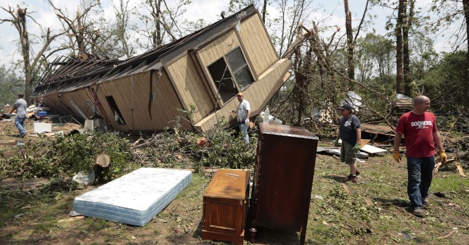 20.mai.2013 - Tornado vira uma casa móvel na cidade de Shawnee, em Oklahoma. O morador, Jean McAdams, teve a ajuda de uma voluntária para retirar os pertences do local. Pelo menos duas pessoas morreram e outras 20 ficaram feridas por causa da tempestade