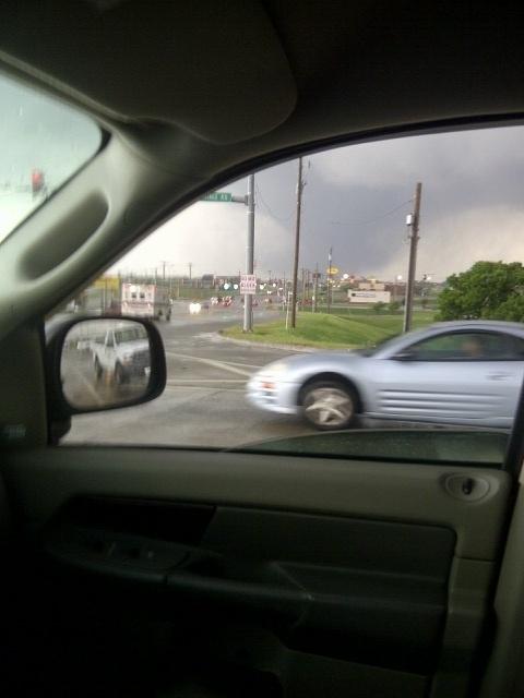 21.mai.2013 - De dentro do carro, a família da brasileira Vânia Pacini, que vive em Oklahoma City (EUA), registra a formação do tornado (à direita) que devastou a cidade norte-americana. Segundo Vânia, ela estava em frente à escola de seu filho mais novo quando as sirenes de alerta da região começaram a tocar