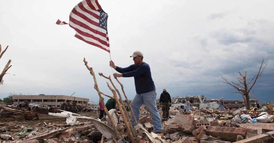21.mai.2013 - Homem coloca bandeira americana em meio aos encombros de uma casa em Moore, nos Estados Unidos, após a passagem de um tornado que devastou a região. O desastre natural deixou dezenas de mortos