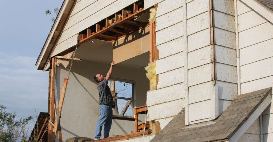 21.mai.2013 - Homem tenta arrumar casa destruída com a passagem do tornado que devastou Oklahoma City, nos Estados Unidos. O desastre naturou deixou dezenas de mortos na região