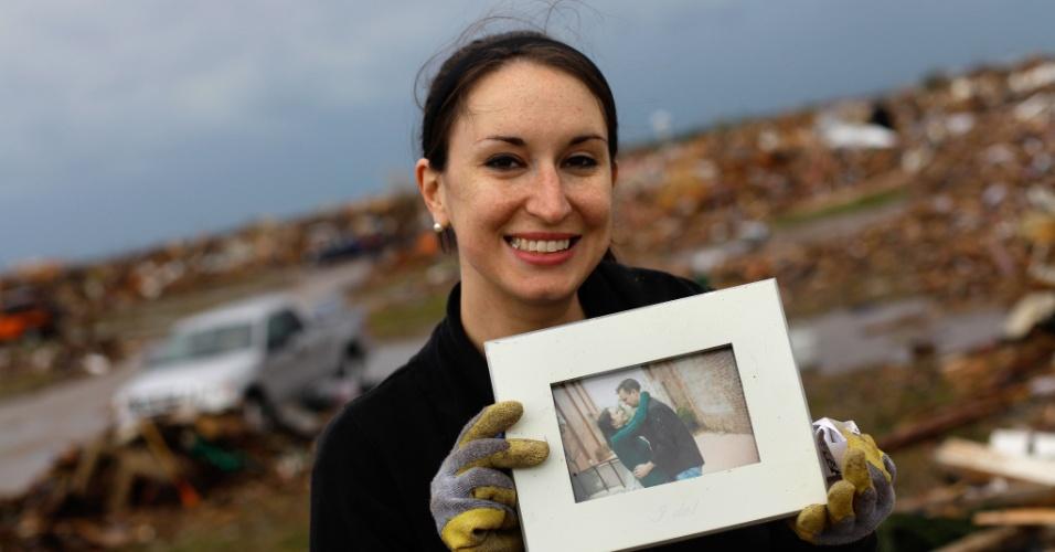 21.mai.2013 - Mulher encontra porta-retrato em meio as escombros de sua casa em Moore (EUA), após a passagem de um tornado que devastou a cidade norte-americana. O desastre natural deixou dezenas de mortos