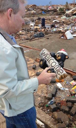 21.mai.2013 - O prefeito de Oklahoma, Mick Cornett, observa objeto retirado dos escombros das casas devastadas pelo tornado que atingiu a cidade norte-americana de Moore.O desastre natural deixou dezenas de mortos