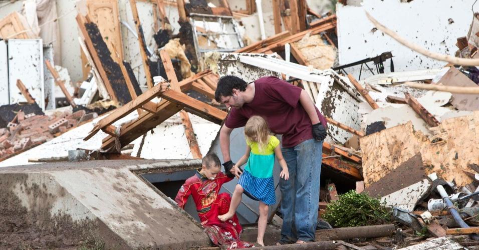 21.mai.2013 - Pai ajuda crianças a sair de abrigo em Moore, nos Estados Unidos, um dia após a passagem do tornado que devastou a cidade norte-americana. O desastre natural deixou dezenas de mortos