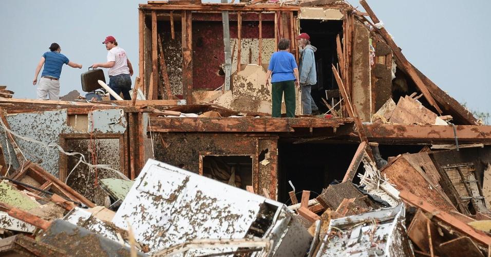 21.mai.2013 - Pessoas procuram por pertences em casa destruída da cidade de Moore, Oklahoma, atingida por tornado no domingo (19). Ao menos 91 pessoas, 20 delas crianças, morreram em consequência da passagem de tornados pelo centro-sul dos Estados Unidos desde então