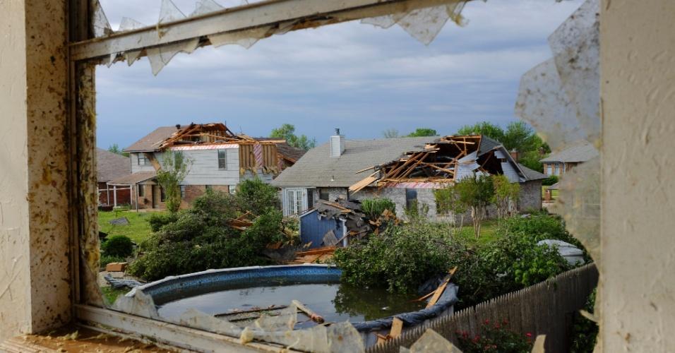 21.mai.2013 - Sinais da destruição provocado pelo tornado que atingiu Oklahoma City, nos Estados Unidos, são vistos de uma janela com a vidraça quebrada. O desastre natural deixou dezenas de mortos na região