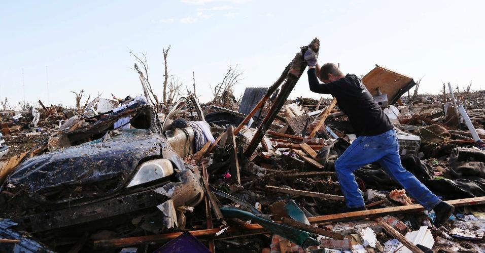 22.mai.2013 - Homem levanta pedaços de detritos da casa de sua mãe que fica na rua da Escola Primária Plaza Towers, destruída após o tornado que devastou a cidade de Moore, no Estado de Oklahoma (EUA), matando pessoas, incluindo crianças, e deixando feridos