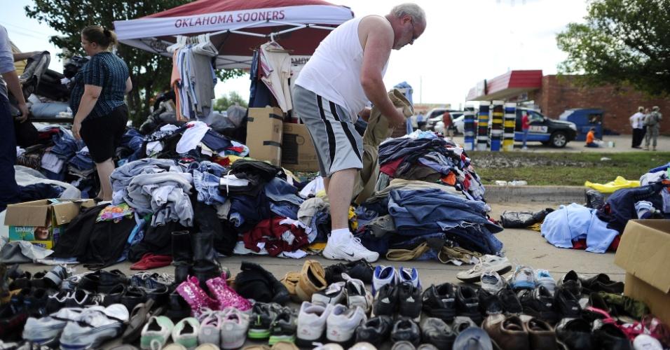22.mai.2013 - Vítima mexe em pilha de roupas em um posto de apoio às vítimas do tornado que atingiu o Estado americano de Oklahoma no último dia 20
