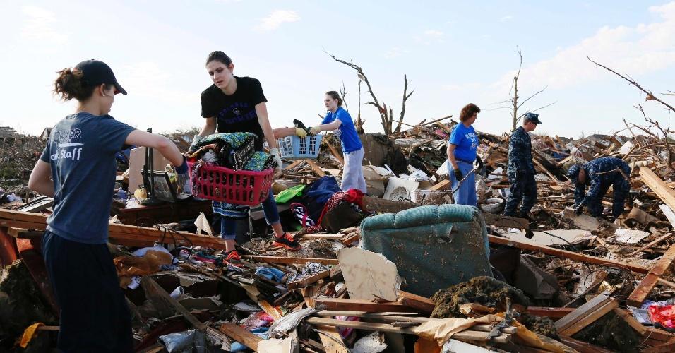 22.mai.2013 - Voluntários resgatam roupas e outros itens para serem encaminhados a desabrigados após tornado que atingiu a cidade de Moore, em Oklahoma, nos Estados Unidos. Equipes de resgate continuam na busca por sobreviventes da tragédia que matou dezenas de pessoas, inclusive crianças, e deixou centenas de feridos