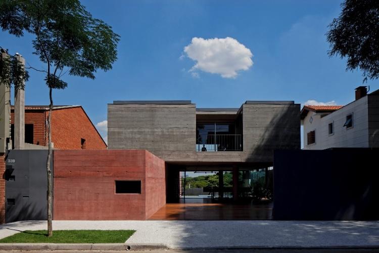 Dois robustos blocos de concreto e varandas reentrantes marcam a fachada frontal da Casa Boaçava, projeto do escritório de arquitetura Una, em São Paulo. O volume superior se apoia, de um lado, no maciço lateral e, do outro, em pilares circulares que ajudam a formar amplos vãos