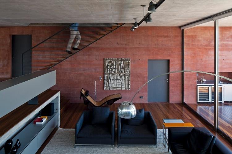 Na Casa Boaçava, em São Paulo, a parede de concreto cor de taipa é estrutural e ornamental ao mesmo tempo. A tonalidade foi obtida com a introdução de óxido de ferro ao concreto fresco, após um trabalho meticuloso de dosagens de pigmentos. O acesso à copa e cozinha se dá por uma porta de ferro encravada na parede vermelha. Já o acesso ao pavimento superior ocorre pela escada metálica com degraus de madeira. O projeto é de autoria dos arquitetos do escritório Una