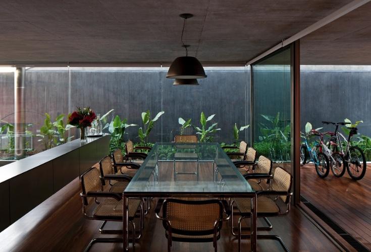 Na Casa Boaçava, em São Paulo, os ambientes sociais são fluídos, separados por portas de correr de vidro transparente. O mesmo piso de madeira foi utilizado desde a garagem, logo na entrada, até a piscina nos fundos. O projeto é do escritório de arquitetura Una