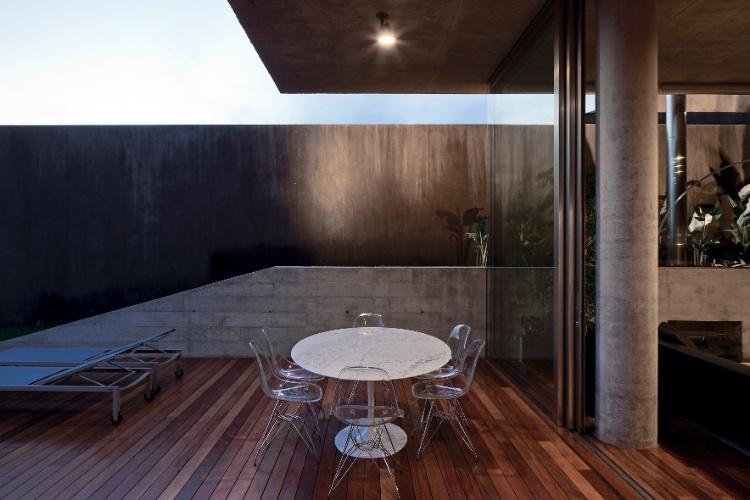 Na Casa Boaçava, entre o deck da piscina e a sala de estar, foi criado um espaço para refeições ao ar livre protegido pela laje de concreto em balanço. O projeto é de autoria dos arquitetos do escritório paulistano Una