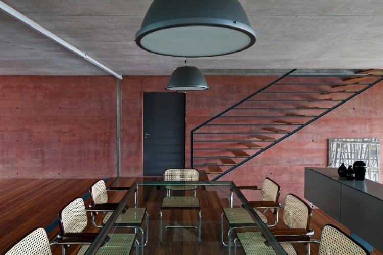 Na sala de jantar da Casa Boaçava duas coisas chamam a atenção: o concreto pigmentado e a escada metálica. O acesso à copa e à cozinha se dá por uma porta de ferro encravada na parede vermelha. O projeto é dos arquitetos do escritório paulistano Una