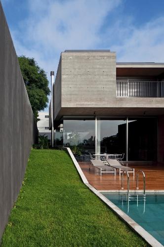 Um corredor gramado acompanha o desnível da casa em toda a lateral do terreno. A Casa Boaçava é projeto do escritório de arquitetura paulistano Una