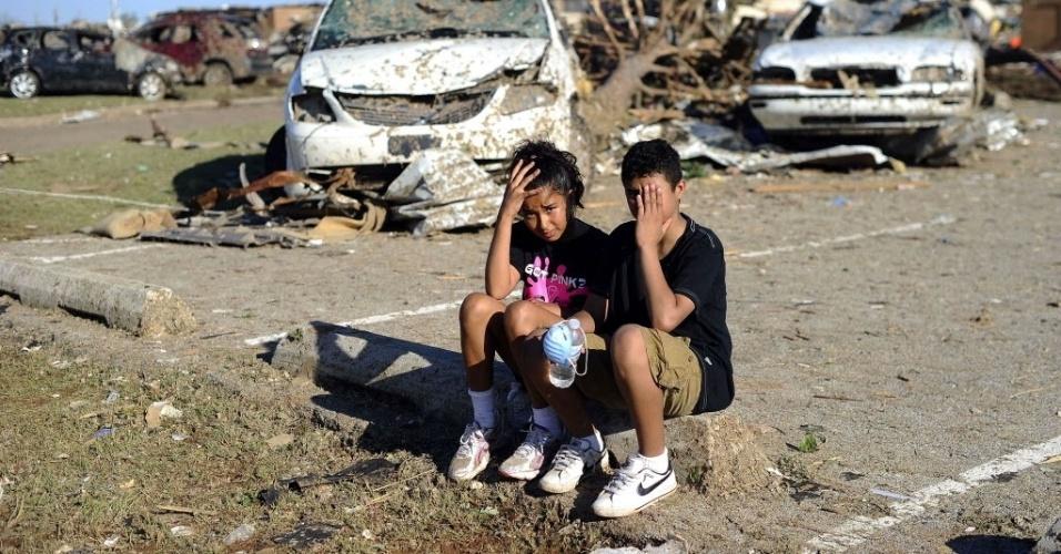 23.mai.2013 - Estudantes da escola Plaza Towers sentam-se no estacionamento do estabelecimento, em ruínas após a passagem de poderoso tornado, em Moore, Oklahoma, EUA. Sete crianças morreram nessa escola, sendo 10 o total de crianças vítimas do tornado no Estado