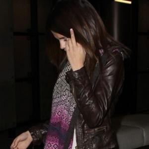 1.mar.2011 - Ao ser fotografada em um shopping de Beverly Hills, ao lado de Justin Bieber, no dia do aniversário de 17 anos do cantor, a cantora e atriz Selena Gomez não gostou da presença do fotógrafo e, discretamente, mostrou o dedo do meio