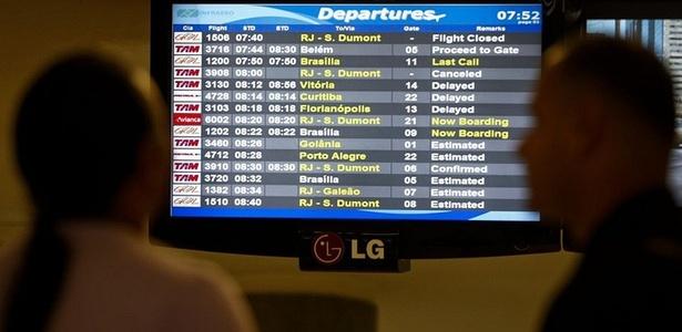 Passageiros observam painel com situação dos voos (Foto: Apu Gomes/Folhapress)