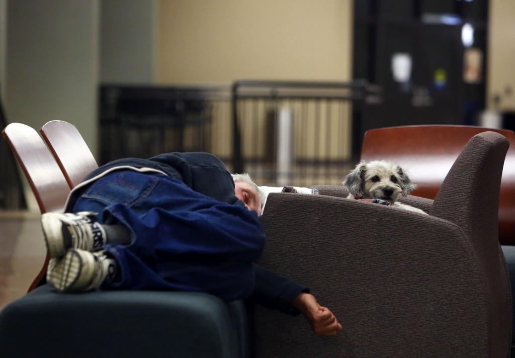 A man and his dog sleep on a makeshift bed at a recreational centre in Lac la Biche, Alberta on May 5, 2016 after fleeing forest fires north of Fort McMurray. Raging wildfires pressed in on the Canadian oil city of Fort McMurray Thursday after more than 80,000 people were forced to flee, abandoning fire-gutted neighborhoods in a chaotic evacuation. No casualties have been reported from the monster blaze, which swept across Alberta's oil sands region driven by strong winds and hot, dry weather. / AFP PHOTO / Cole Burston