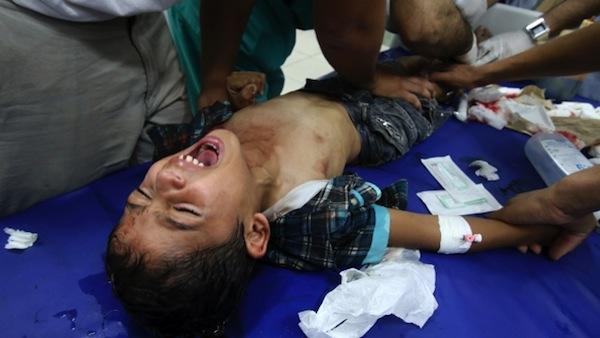 Médicos palestinos seguram menino que teria sido ferido em um ataque israelense (Ibraheem Abu Mustafa/Reuters)