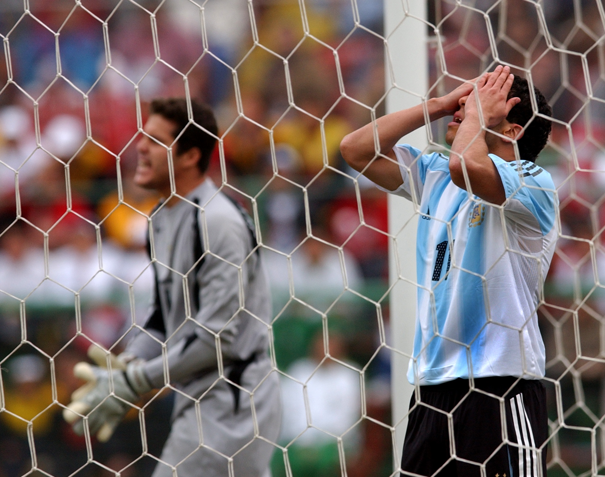 Carlos Tevez of Argentina covers his face after missing a chance on goal as Brazil's goalkeeper Julio Cesar is seen at left during their final game of the Copa America, in Lima, Peru, Sunday, July 25, 2004. (AP Photo/Natacha Pisarenko)