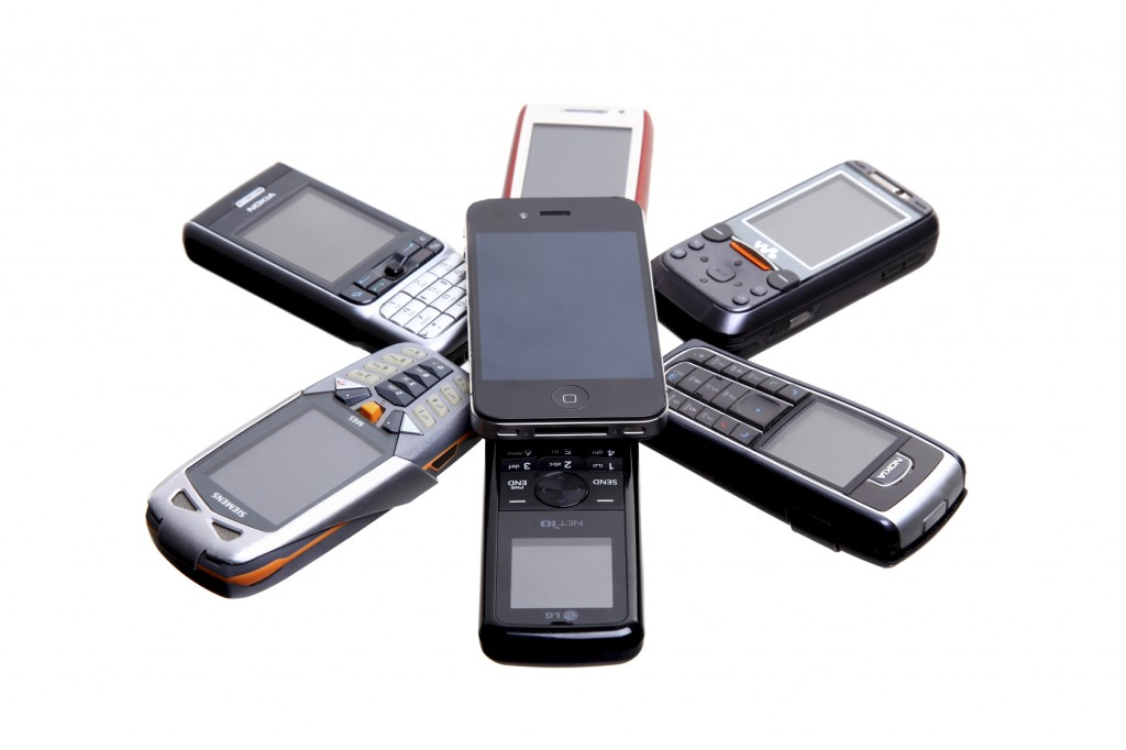 """London, United Kingdom - October 31, 2011: A collection of various mobile phones on a plain background including Nokia, Siemens and Sony Ericsson and iphone"""