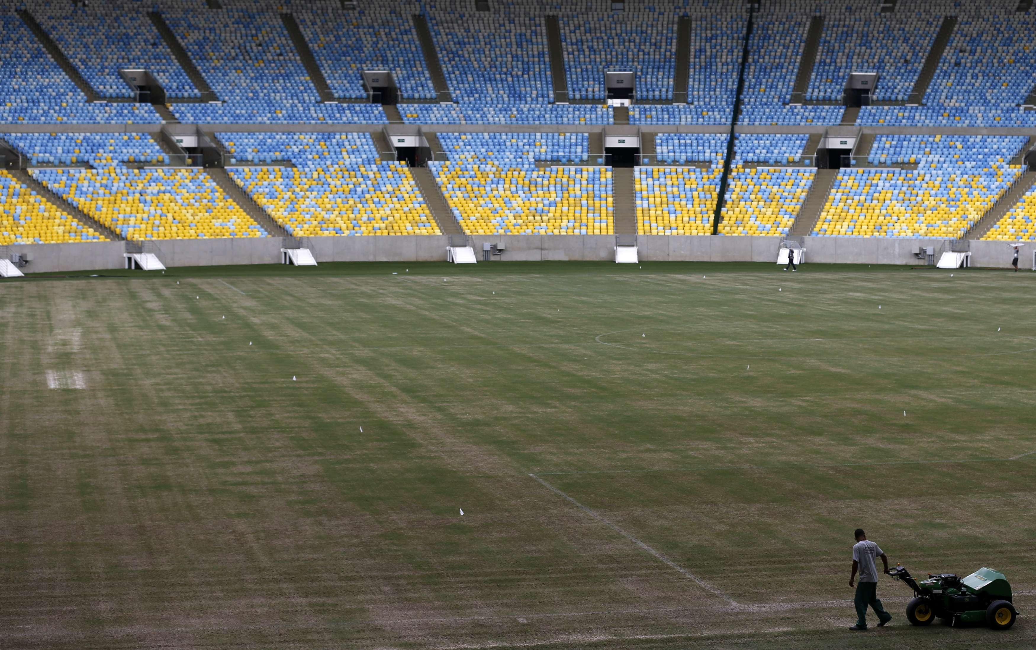 A worker prepares the field of the Maracana stadium during a press visit in Rio de Janeiro