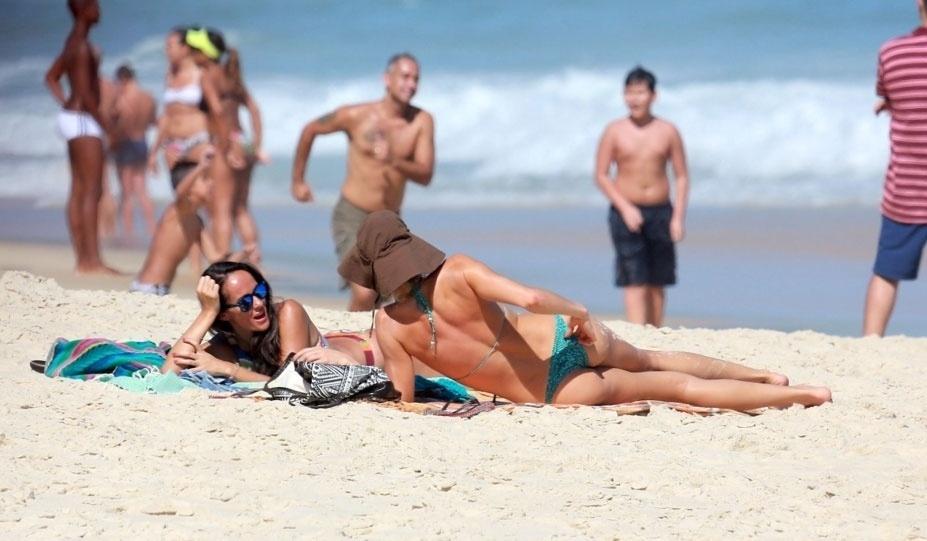 31.out.2015 - Grazi Massafera curte a praia de São Conrado, zona sul do Rio de Janeiro, ao lado de uma amiga. A atriz foi flagrada dando uma ajeitadinha no biquíni