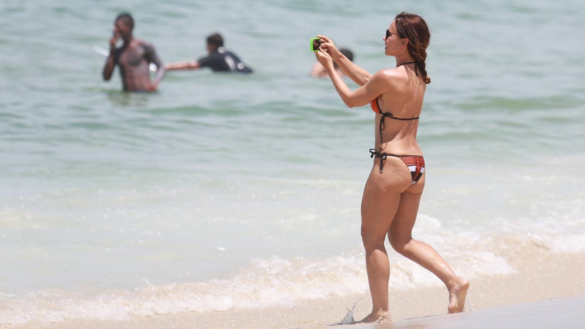 28.fev.2016 - Carla Marins é flagrada tirando fotos enquanto brincava com a família na praia da Barra da Tijuca, no Rio de Janeiro