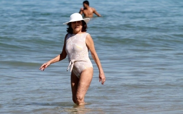 """7.jul.2013 - Após rebater os críticos sobre o uso do biquíni, Betty Faria, 72, aproveitou o sol de maiô na praia do Leblon, no Rio. Recentemente, em entrevista à revista """"LOLA"""", a atriz falou sobre os comentários maldosos que recebeu após usar biquíni na praia: """"Velha baranga, dessituada, sem espelho, e outras ofensas que, passada a raiva, me fizeram pensar na burca. Então querem que eu vá à praia de burca, que eu me esconda, que me envergonhe de ter envelhecido? E a minha liberdade?"""", desabafou. """"Depois de tantas restrições alimentares, remédios para tomar, exercícios a fazer, vícios a evitar, todos próprios da idade, ainda preciso andar de burca? E o prazer, a alegria, meu humor?"""", completou a atriz. Pelo traje escolhido para o passeio, parece que as críticas realmente abateram Betty."""