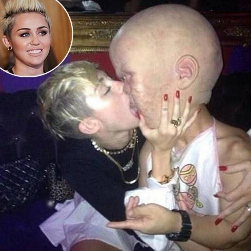 """1.ago.2013 - O que parece ser assustado é apenas uma brincadeira. Na imagem, a cantora e atriz Myley Cyrus beija um rapaz vestido de """"bebê gigante"""" em uma festa na boate Beacher's Madhouse em Los Angeles, nos Estados Unidos. A foto foi divulgada na madrugada desta quinta-feira por Paris Hilton. Miley costuma frequentar a casa noturna, famosa por apresentações de cabaré"""
