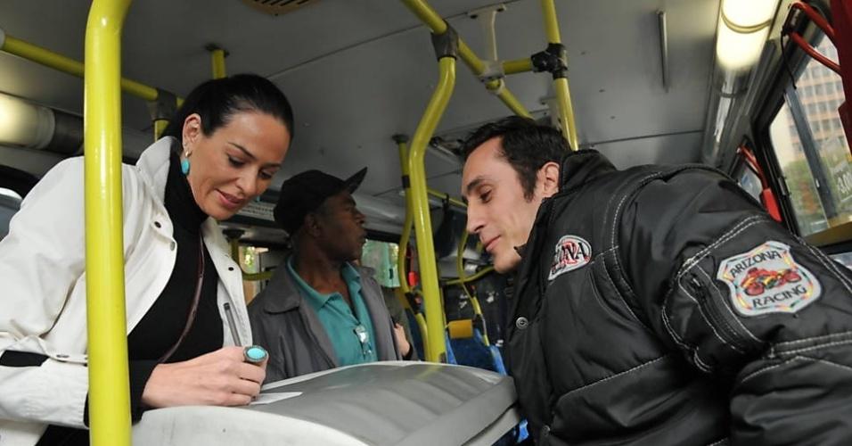 """1.out.2013 - Cozete Gomes foi convidada pela """"Folha de S. Paulo"""" para andar de transporte coletivo pela cidade de São Paulo. No trajeto foi reconhecida pelo cobrador, Israel Guilger, 29, a quem presenteou com um postal com foto sua que carregava na bolsa da marca Versace. """"Achei o cobrador e o motorista do ônibus educadíssimos"""", disse. """"Os passageiros, apesar do cansaço, também"""". Ao comentar sobre sua experiência com a empregada, Bernadete, ouviu em resposta: """"Para quem leva pisão no pé, mão-boba e encoxada, na faixa ou não, um fusquinha seria o paraíso. Prefiro ficar horas num carro parado no trânsito, sentada no conforto, do que levar desaforo dentro de busão. Vai pegar o ônibus na periferia de manhãzinha ou no fim do dia para ver o quanto é bom"""", comentou a empregada"""