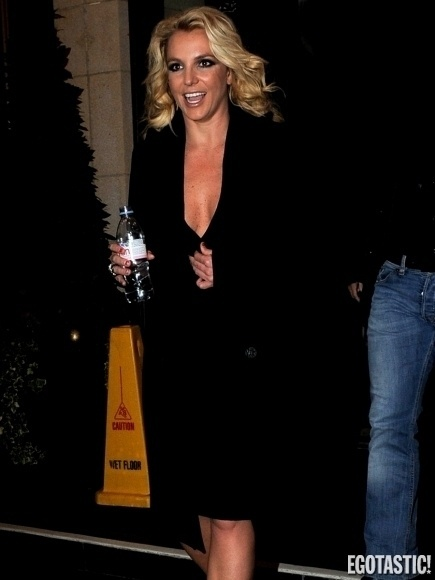 19.out.2013 - Com um decote bastante ousado, Britney Spears se esforçou para não deixar à mostra parte dos seios para os paparazzi que a aguardavam durante sua passagem por Londres, onde foi clicada deixando o hotel onde estava hospedada