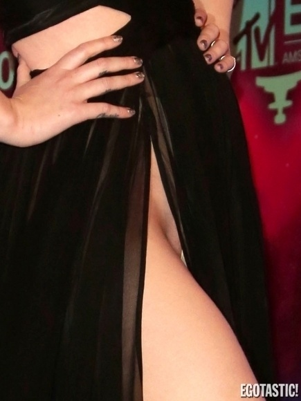 10.nov.2013 - A rapper Iggy Azelea usou look bem ousado para passar pelo tapete vermelho do Europe Music Awards, que aconteceu em Amsterdã, capital da Holanda. Sem calcinha, ela abriu a fenda do vestido e mostrou tudo. Para quem não sabe, antes de Miley Cyrus, Iggy já fazia o famoso twerk em seus videoclipes e apresentações
