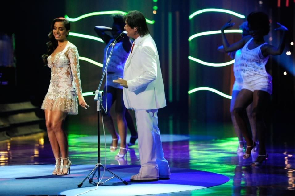 """23.nov.2013 - Em especial de fim de ano da Globo, Roberto Carlos surpreendeu a todos ao cantar uma versão da música """"Show das Poderosas"""" com Anitta. """"Gente, olha só: estou cantando com o Roberto Carlos! Quase desafinei umas cinco vezes. Estou me sentindo poderosa"""", disse a cantora, sendo imediatamente elogiada pelo cantor: """"Mas você é"""". Depois de cantarem juntos, Roberto brincou e disse que ficou """"babando"""", referindo-se ao refrão da música"""