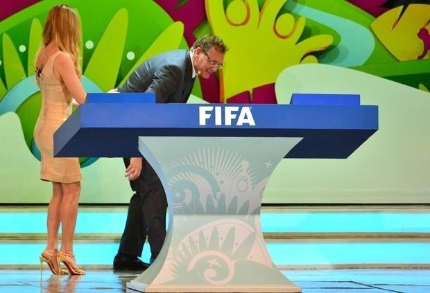 6.dez.2013 - Na imagem, Fernanda Lima e o secretário-geral da Fifa, Jérôme Valcke, que se abaixa para uma das bolinhas durante apresentação do sorteio dos grupos da Copa de 2014