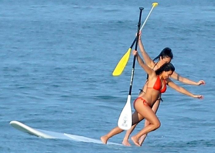 20.ago.2014 - Kim Kardashian foi flagrada curtindo o mar de uma praia mexicana. Na imagem, a socialite norte-americana perde o equilíbrio enquanto praticava paddle boarding. Kim estava acompanhada de sua assistente,  Stephanie