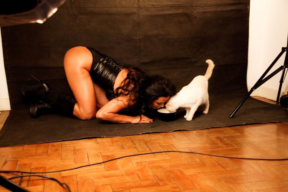 """25.set.2014 - A morena Carla Prata, ex-repórter do """"Domingão do Faustão"""", fez um ensaio sensual bem ousado que despertou o seu lado """"felina sexy"""". Trajada com um espartilho de couro, ela mostrou que está com tudo em cima, deixando suas curvas à mostra e empinando o bumbum na hora de dividir uma tigela de leite com uma gata de estimação"""