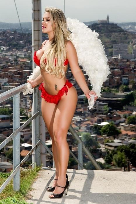 29.out.2014 - Gil Jung parou o Complexo do Alemão, no Rio, para um ensaio sensual de lingerie. Vestindo um conjuntinho vermelho, a modelo usou asas para completar o figurino.