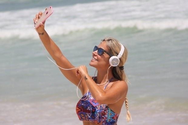 3.fev.2015 - Após reforçar o bronzeado, a atriz Robertha Portella aproveitou para tirar uma selfie na praia da Barra, no Rio de Janeiro