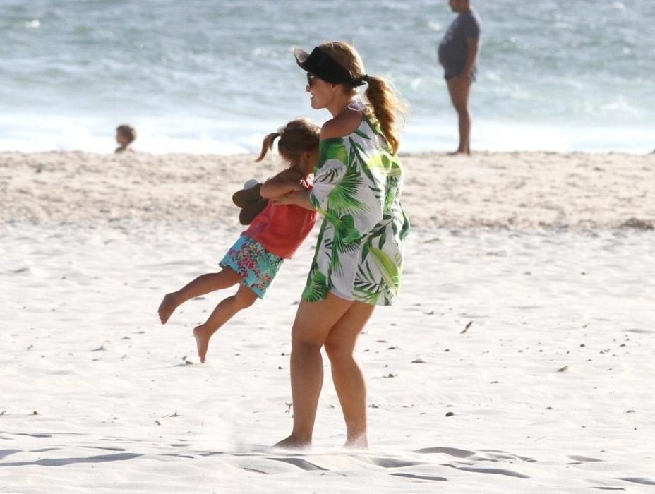 1.fev.2015 - Luciano e Angélica aproveitaram o domingo ensolarado para passear com a filha caçula, Eva, de 2 anos. O casal andou de bicicleta (a pequena foi na garupa com o papai) e também relaxou um pouco nas areias da praia na Barra da Tijuca, no Rio de Janeiro, com a garotinha