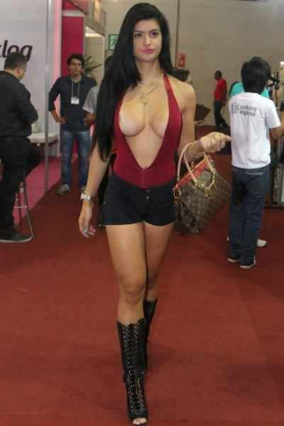 """8.mar.2015 - Enquanto circulava com uma mega decote pelos estandes da Erótika Fair, feira do mercado erótico que aconteceu em São Paulo, a modelo Camila Vernaglia acabou """"pagando peitinho"""". Também pudera, era muito pouco tecido para tanta """"comissão de frente"""""""