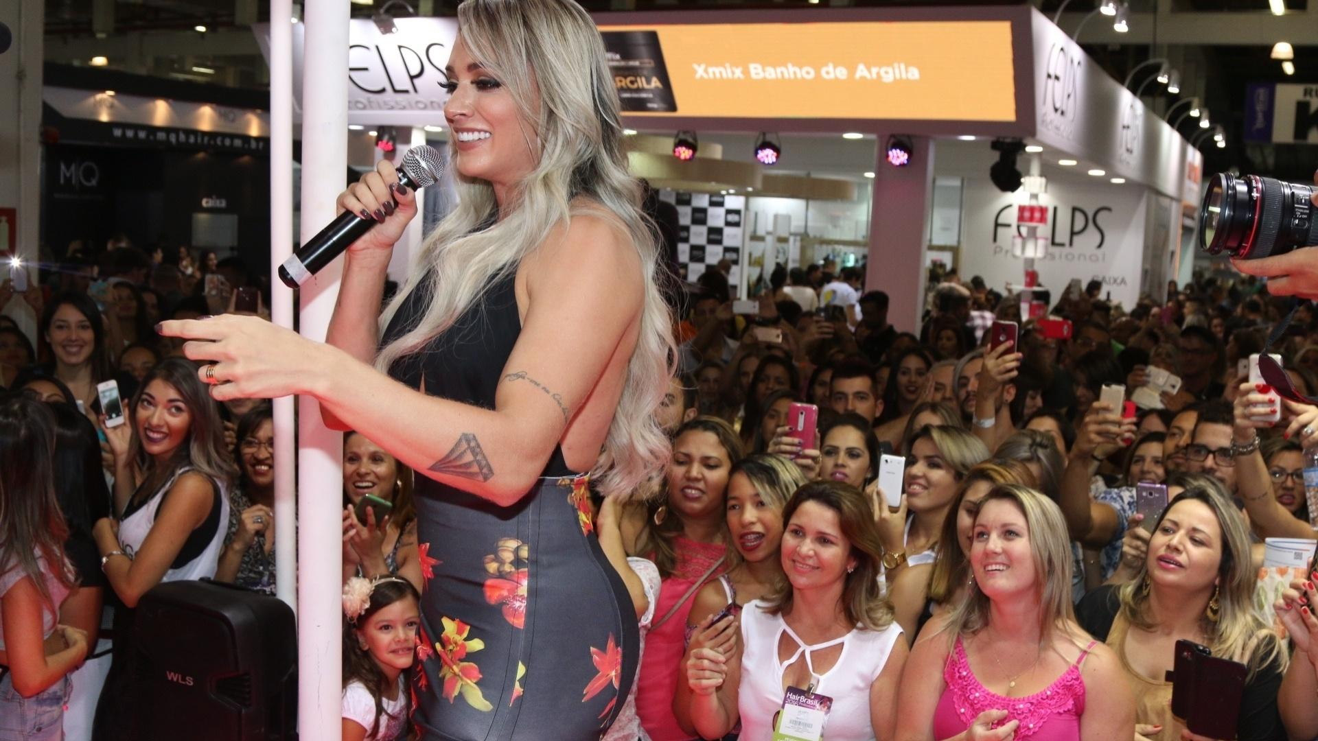 17.abr.2016 - Juju Salimeni marcou presença na feira Hair Brasil, em São Paulo. Decotadíssima, a loira quase mostrou demais ao chegar no stand de uma das marcas que estão expostas no evento.