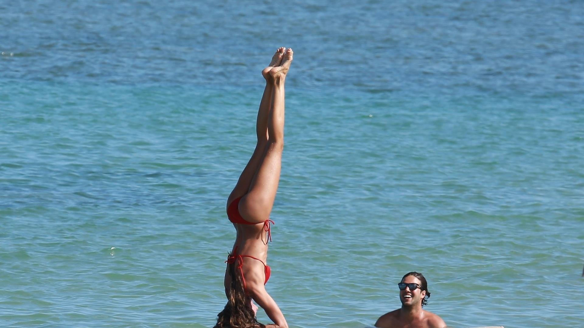 5.jan.2016 - A top brasileira Izabel Goulart deu um show de equilíbrio sobre uma prancha de surfe na praia de Trancoso, na Bahia