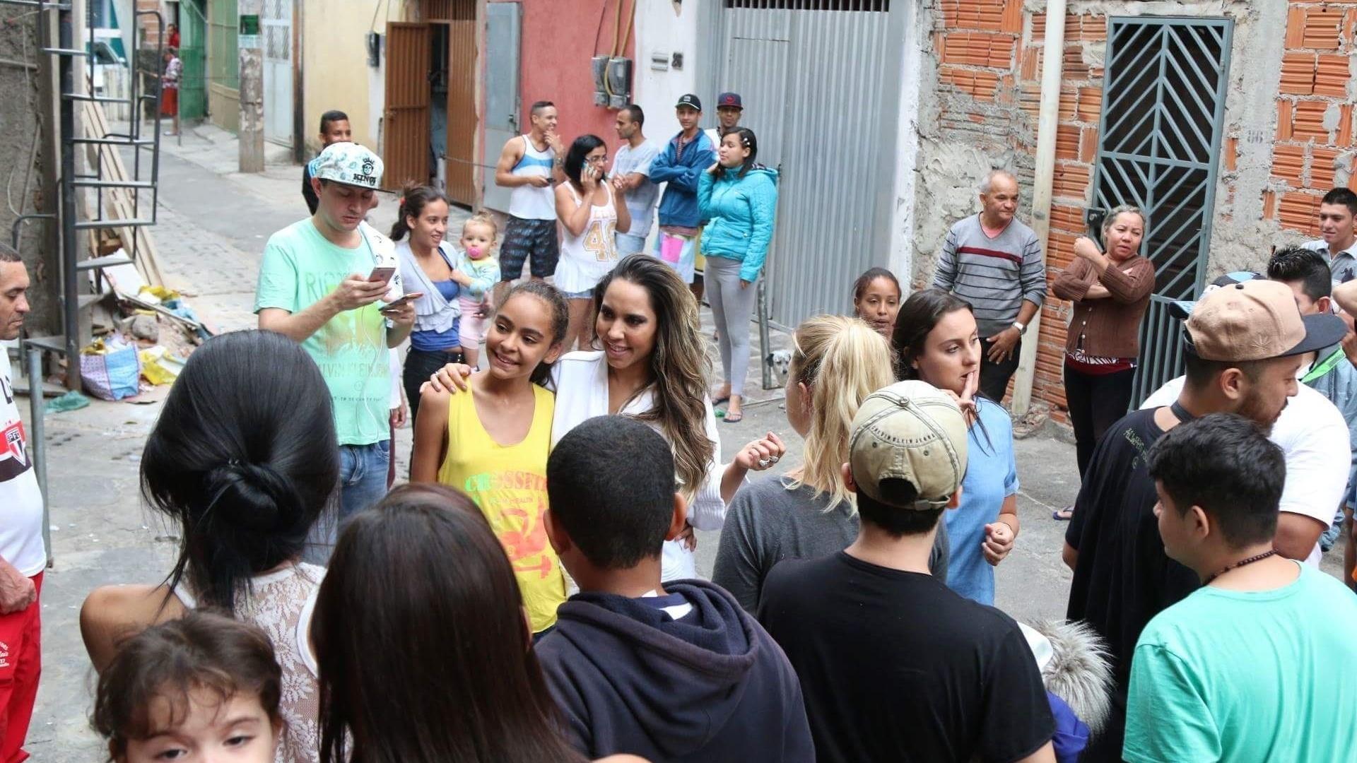 5.mai.2016 - Renata Frisson, a Mulher Melão, interage com os moradores da comunidade de Heliópolis, zona sul de São Paulo, durante ensaio para a revista Sexy